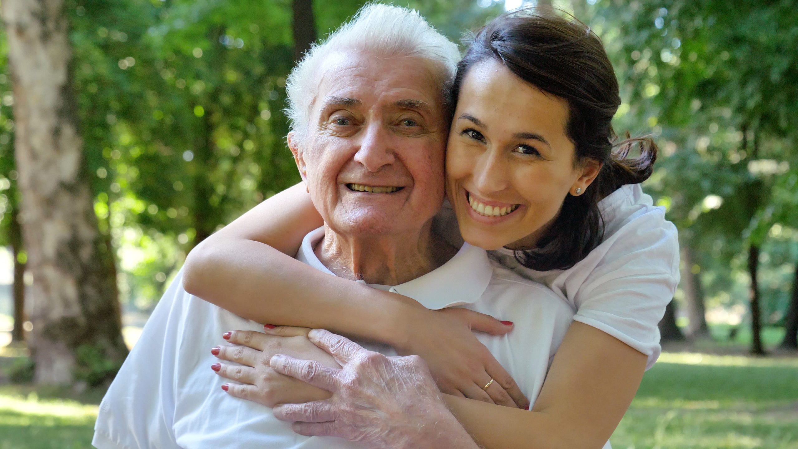 Granddaughter, nurse, caring for the elderly, girl (woman) from senior care plus hugging grandfather, smiling, happy, walking in the park. Concept: boarding house, sanatorium, a house for the elderly, help for the elderly.