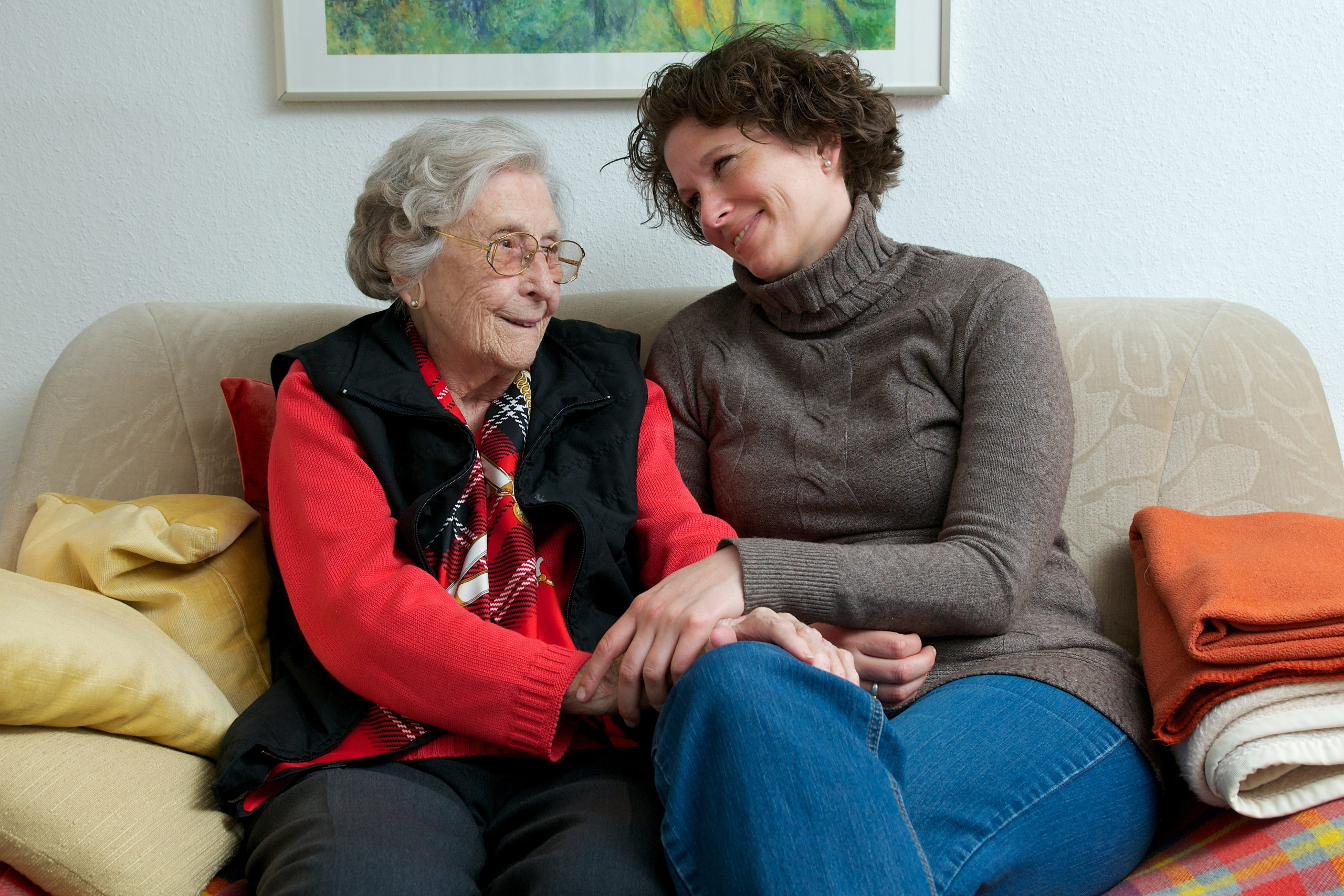 senior care plus caregiver with elderly cliient holding hands on sofa happy