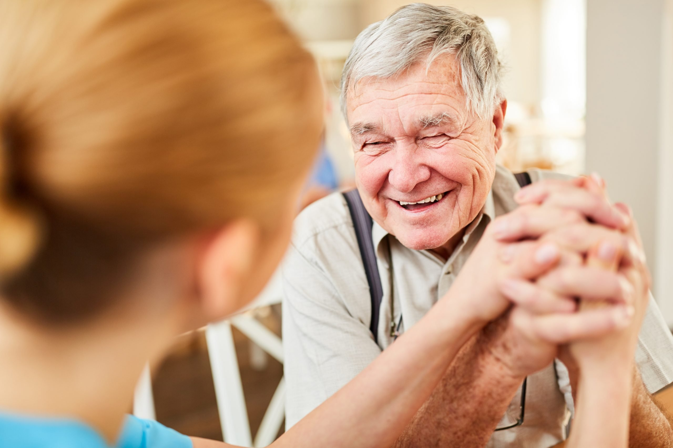 Aged man gets hope and is happy from a senior care caregiver
